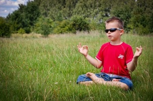 Boy in sunglasses meditating
